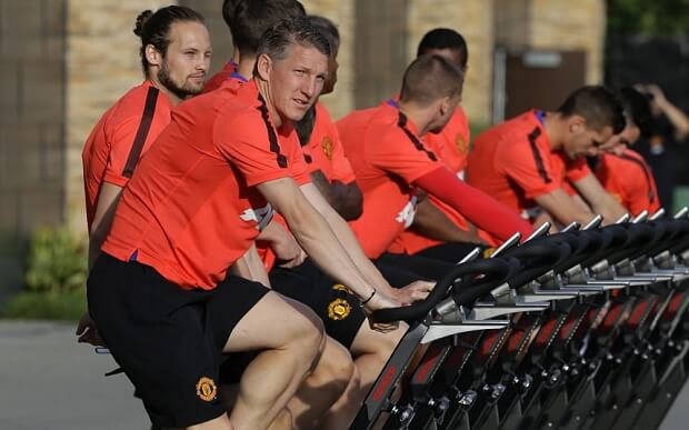 Recent Manchester United signee Bastian Schweinsteiger, left, rides a stationary bike with his teammates during training Thursday, July 16, 2015, in Renton, Wash. Manchester United is in the Seattle area for an international friendly soccer match against Mexico's Club America to be played Friday. (AP Photo/Ted S. Warren)