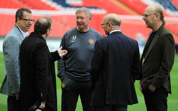 Manchester United directors Bryan Glazer (left), Avram Glazer (right) and Joel Glazer (second right) speak with manager Sir Alex Ferguson (centre)