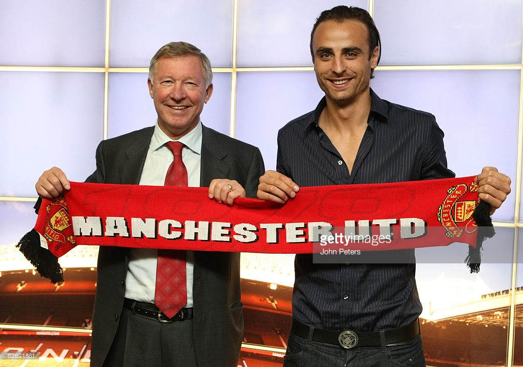 MANCHESTER, ENGLAND - SEPTEMBER 1: Dimitar Berbatov poses with Sir Alex Ferguson and a Manchester United scarf after signing for the club at Old Trafford on September 1 2008 in Manchester, England. (Photo by John Peters/Manchester United via Getty Images) *** Local Caption *** Dimitar Berbatov;Alex Ferguson