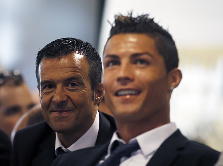 Real Madrid's Cristiano Ronaldo (R) reacts while watching a video as he sits next to his agent Jorge Mendes during a ceremony at Santiago Bernabeu stadium in Madrid September 15, 2013. Ronaldo has agreed a contract extension with Real Madrid, the La Liga club said on Sunday. REUTERS/Sergio Perez (SPAIN - Tags: SPORT SOCCER)