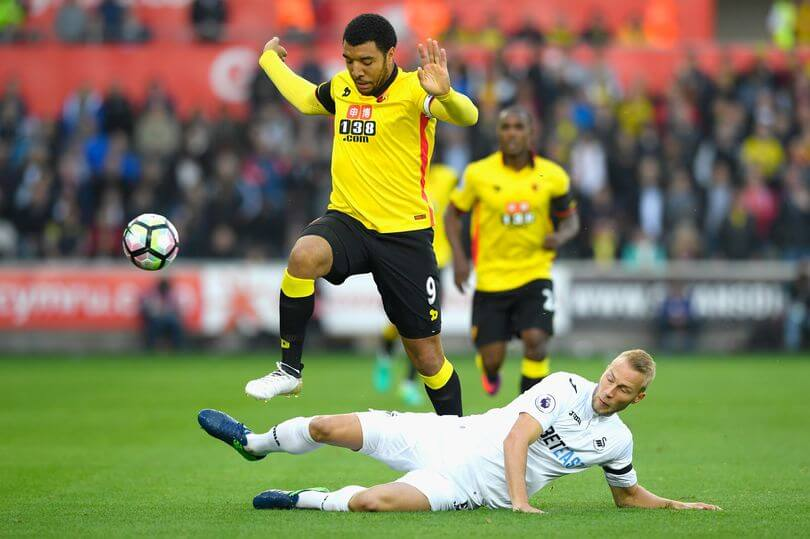 troy-deeney-of-watford-is-tackled-by-mike-van-der-hoorn-of-swansea